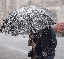 Image of person with umbrella in falling snow