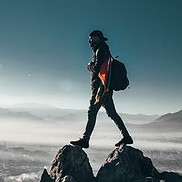 Image of person walking on high mountaintop