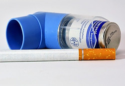 Image of an inhaler lying next to a cigarette